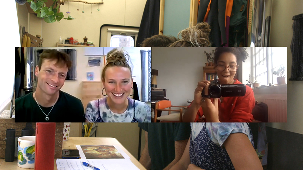 Film still showing artists Jade Montserrat and Webb-Ellis on a zoom call. Jade holds a small video camera, they are all smiling.